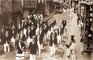 Por la calle Larretxipi, la Tamborrada con Juanita Mancisidor de cantinera y Manueltxo Izaguirre de Sargento